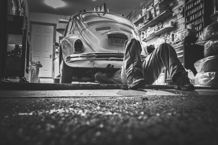 Picture showing a mechanic working underneath a car