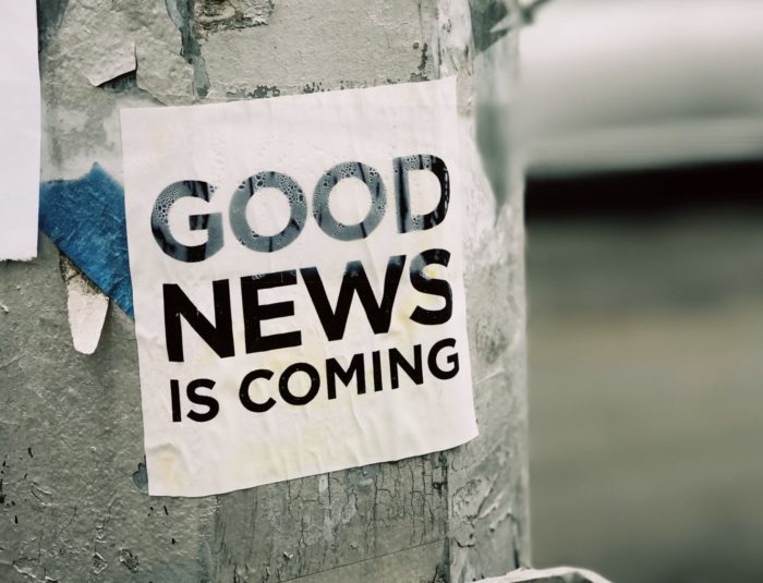 "Picture showing a sign stuck to a tree, saying ""Good news is coming""."